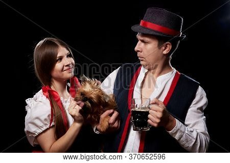 Happy Oktoberfest Couple In National Ethnic Dress With Mug Of Beer, Small Shaggy Dog On Black Backgr