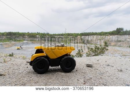 Yellow Mining Truck With Stones At High Mountain Near Quarry. Landscape At Opencast. Blue Sky With C