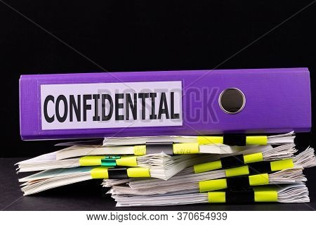 Text, Word Confidential Is Written On A Folder Lying On Documents On An Office Desk.
