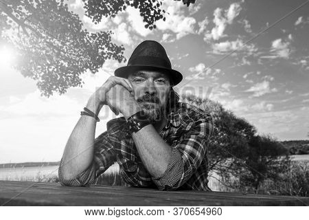 Handsome Man With A Black Stylish Hat Sitting On A Wooden Bench In A Beautiful Natural Parkland. Hap