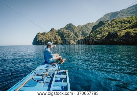 Back View Of The Man Enjoying Nature On The Boat And Looking At Tropical Island. Travelling Tour In