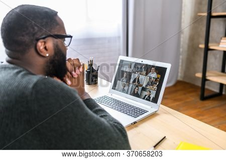 Video Chat With Employees. Concentrated African-american Guy In Glasses On Online Meeting With Many
