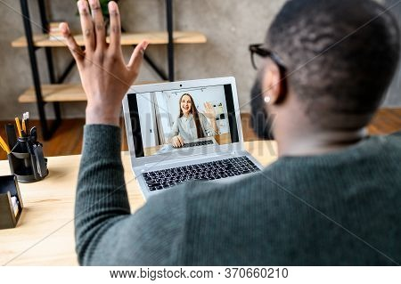 Video Chat With Employee. Cheerful African-american Guy In Glasses Waving Hello To Female Coworker O