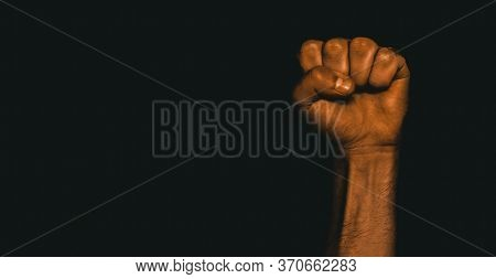Male Black Fist On A Black Background. Aggressiveness, Masculinity, The Concept Of Challenge.