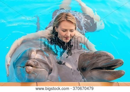 Young Girl Hugs Two Dolphins At The Dolphin Therapy Session