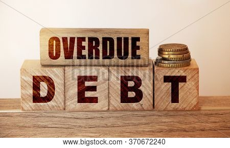 Overdue Debt Words Written On Wooden Cubes And Pill Of Coins. Debts And Loan Business Concept