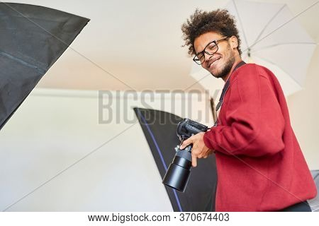 Young man as a professional photographer with camera in the photo studio