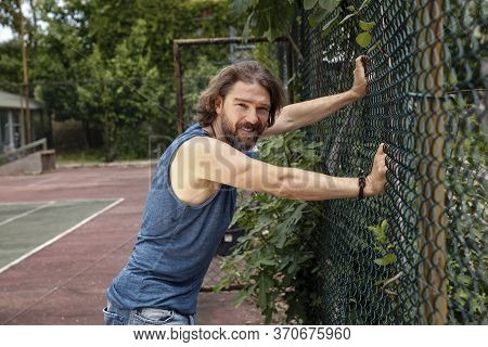 Handsome Man In Blue Tank Top Leaning On The Chainlink Fence With His Hands, Smiling. Man In His 40'