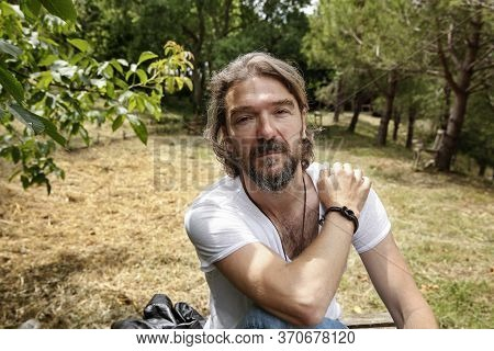 Portrait Of A Handsome Mature Man Sitting On A Wooden Bench In A Natural Parkland. Bearded Man Weari