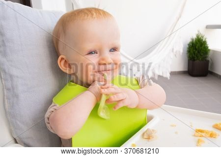 Happy Baby Learning To Eat By Herself, Holding Slice Of Vegetable. Little Child Wearing Plastic Bib,