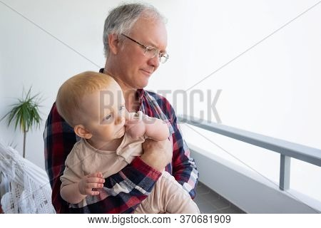 Mature Grandpa Spending Time With Cute Granddaughter, Holding Baby In Arms, Sitting On Balcony. Clos