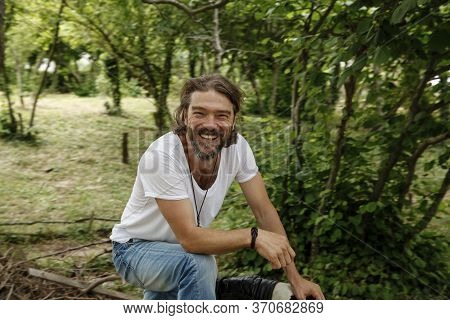 Handsome Mature Man Sitting And Laughing In A Natural Parkland. Bearded And Happy Man Wearing White