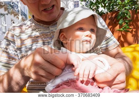 Cute Baby Girl Wearing Summer Hat, Sitting On Grandfather Knees On Outdoor Terrace Or Street Cafe. F