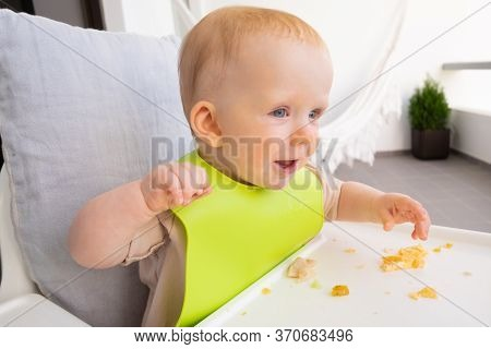 Happy Sweet Baby Wearing Plastic Bib, Sitting In Highchair With Food Messy On Tray. First Solid Food