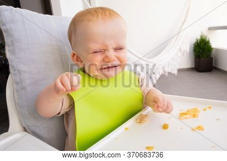 Annoyed Hungry Baby Wearing Plastic Bib, Sitting In Highchair With Food Messy On Tray And Crying Wit