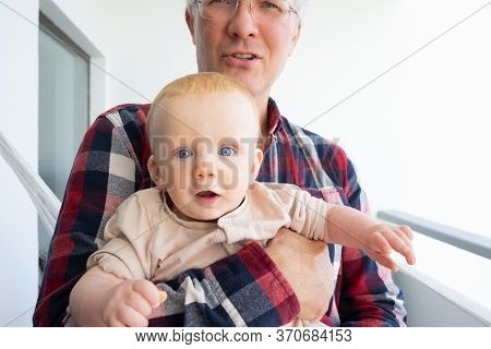 Surprised Excited Cute Baby Sitting On Grandpa Knees And Looking At Camera With Wide Eyes. Closeup S