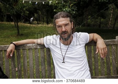 Handsome Mature Man Sitting On A Wooden Bench In A Natural Parkland. Bearded Man In His 40's, Lookin