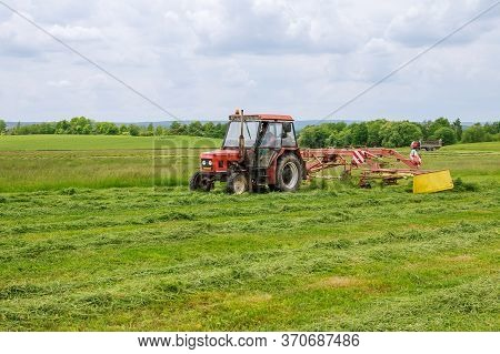Skutech, Czech Republic, 4 June 2020: A Tractor With A Rotary Rake Rakes Freshly Cut Grass For Silag