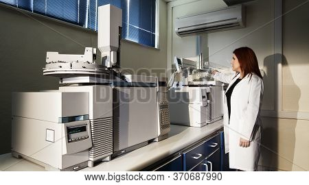 Factory Lab. Woman Doing Research In The Factory, Laboratory. Test Machines In The Lab.