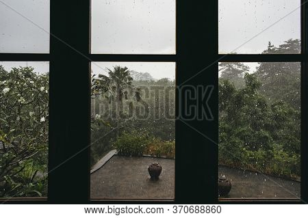 View From The Window Of The House To The Pool And Rainforest With Palm Trees In A Rainstorm.