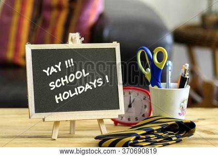 Image Of Happy Holidays Greeting Letters On Brown Mini Notice Board. Besides A Decorative Green Plan