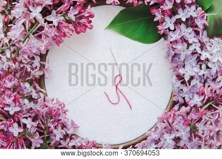 White Canvas For Embroidery With A Needle And Thread In A Wooden Hoop, Beautiful Spring Lilac Flower