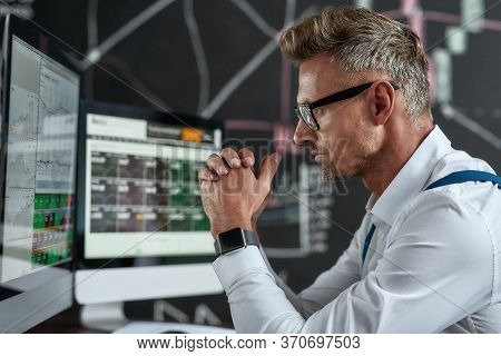 Close Up Of Middle-aged Caucasian Trader Looking Focused While Sitting In Front Of Computer Monitor.