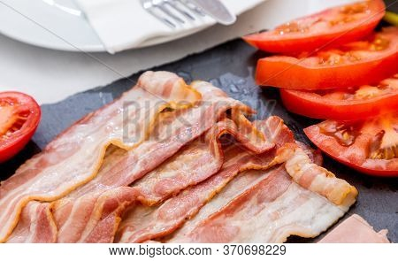 Grilled Bacon And Tomatoes On A Stone Tray Are High-fat Foods Placed On The Breakfast Or Midday Tabl