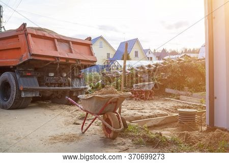 Wheelbarrow With Sand And Shovel In Foreground And Dump Truck Preparing To Dump Sand On Ground In Ba