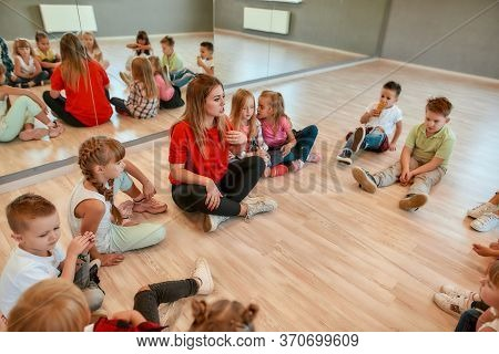 A Group Of Little Dancers Sitting On The Floor Gathered Around Their Female Dance Teacher. Young Fem