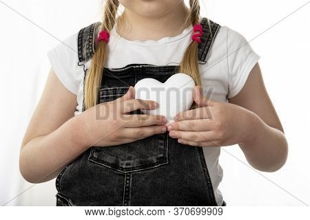 Little Girl Holding A White Heart In Her Hands. Girl Stands On A White Isolated Background