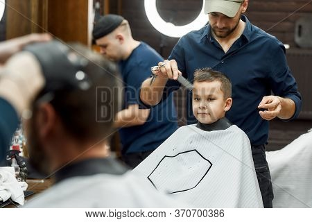 Cute Little Boy Sitting In Armchair In Barbershop While Barber With Scissors And Comb In Hands Doing