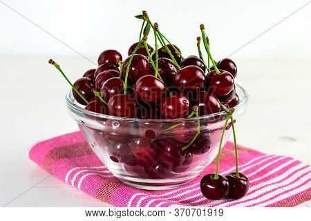 Fresh Sour Cherries In Glass Bowl, Dishcloth And Green Leaves On White Wooden Table. Fresh Ripe Sour