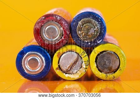 Multiple Used Bad Aa Alkaline Batteries Are Seen Arranged In A Pile On A Reflective Orange Surface.