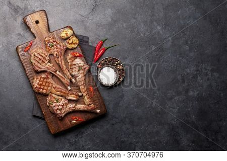 Grilled lamb ribs on cutting board. Hot rack of lamb with spices and condiments. Top view on stone table with copy space