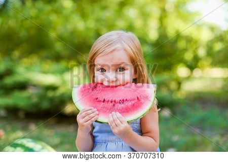 Child Eating Watermelon In The Garden. Kids Eat Fruit Outdoors. Healthy Snack For Children. 2 Years