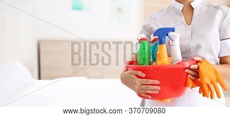 Young Chambermaid Holding Cleaning Supplies In Hotel Room, Closeup View With Space For Text. Banner