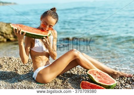 Tanned Young Girl Sits On Pebble Beach Near Sea, Holds Huge Piece Of Ripe Watermelon In Hands, Bites