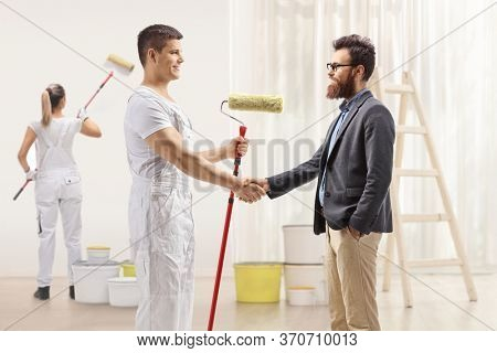 Male painter shaking hands with a bearded man and a female painter painting a wall inside a house