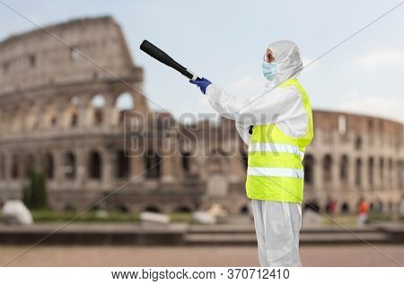 disinfection service and pandemic concept - sanitation worker in protective gear, medical mask, gloves and goggles with pressure washer or sanitizer over coliseum in rome, italy on background