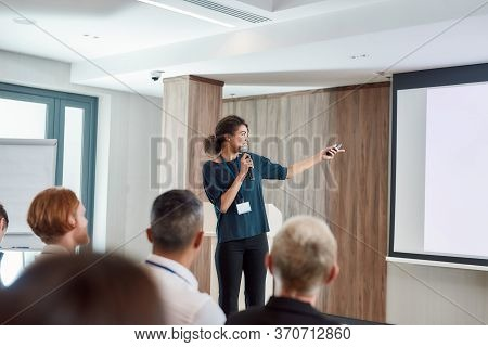 Female Speaker With Laser Pointer Pointing At The Screen While Giving A Talk On Corporate Business M