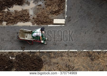 Worker Rests Sitting On The Empty Wheelbarrow, View From The Top. Man In Uniform Near The Heap Of So