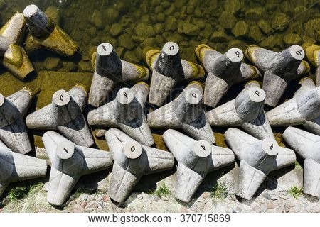 Save Download Preview Concrete Breakwater Blocks Background. Lake Shore Protection Landscape. Gizyck