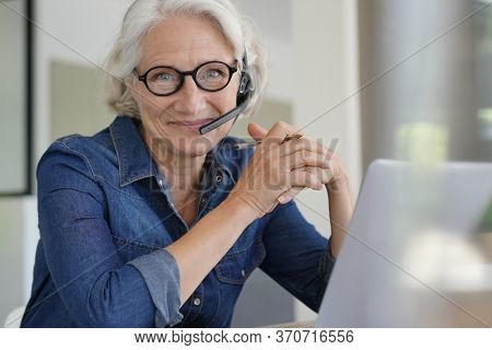 Active senior woman working from home on laptop