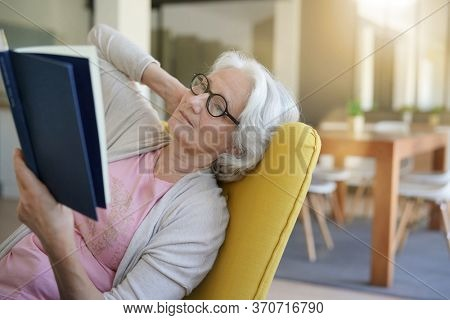 Senior woman relaxing in armchair and reading book