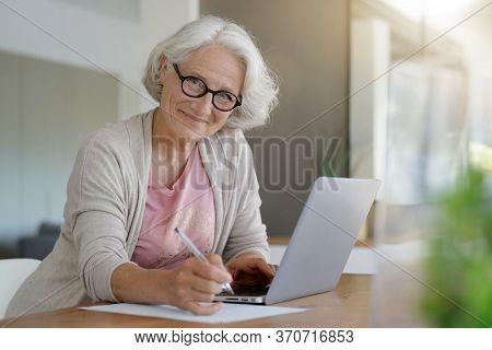 Senior woman using laptop computer at home