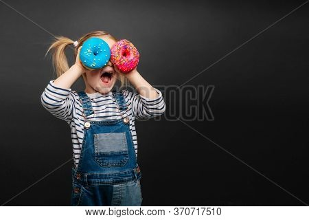 Happy cute girl is having fun played with donuts on black background wall. Bright photo of a child. Colored donuts