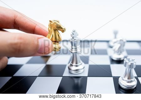 Hand Holding Gold Horse Attack Silver King In Battle On Chess Board.business Leader Concept For Mark
