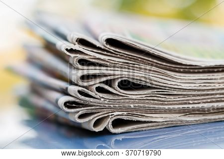 Time To Read Concept. Newspapers Folded And Stacked On The Blue Surface And Blur Background. Closeup