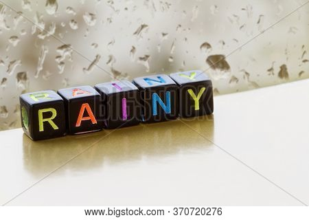 Rainy Weather. The Inscription Rainy From Toy Cubes With Colored Letters On The Background Of A Wind
